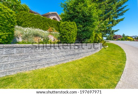 Some flowers and nicely trimmed bushes on the leveled and stoned front yard. Landscape design. - stock photo
