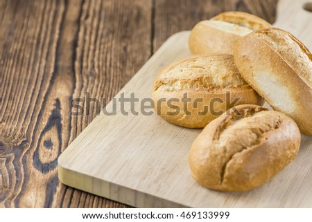 Some fresh baked Rolls (detailed close-up shot) on wooden background (selective focus)