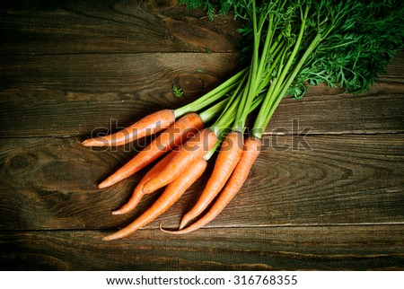 Some fresh carrots at the wooden table - stock photo
