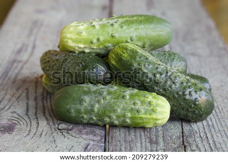 Some fresh cucumbers on a wooden board - stock photo