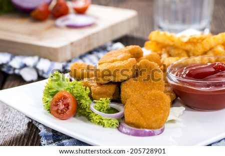 Some fresh made golden Chicken Nuggets with crispy chips - stock photo