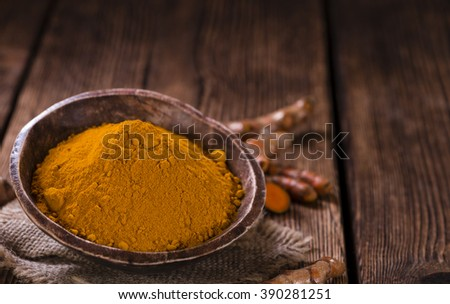 Some fresh Turmeric on an old wooden table (detailed close-up shot, selective focus) - stock photo