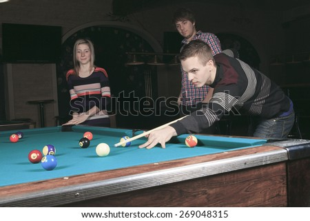 some friends play snooker in a bar. - stock photo