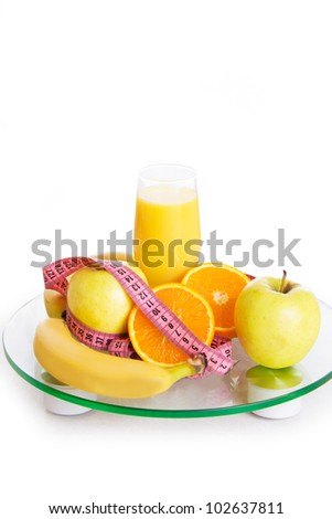 Some fruits, juice and measure tape on scales over white - stock photo