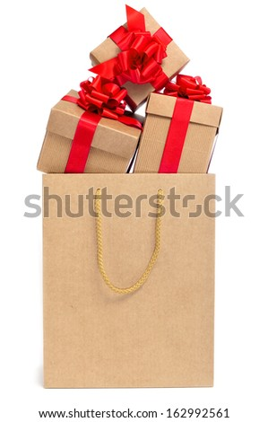 some gifts with red ribbon bows in a shopping bag on a white background  - stock photo