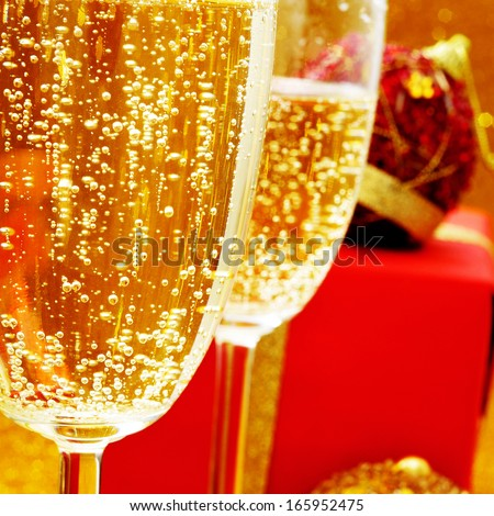 some glasses with champagne and some gifts - stock photo