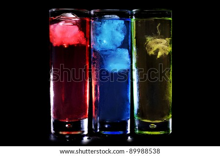 some glasses with cocktails of different colors on a black background - stock photo