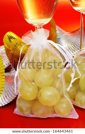 some glasses with spanish champagne and sachets with the twelve grapes of luck, traditional on the New Year in Spain - stock photo