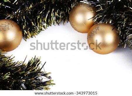 some gold christmas balls in a white background with wreath