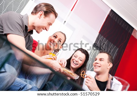 Some good friends sitting together at home having a good time with snacks and soft drinks. - stock photo