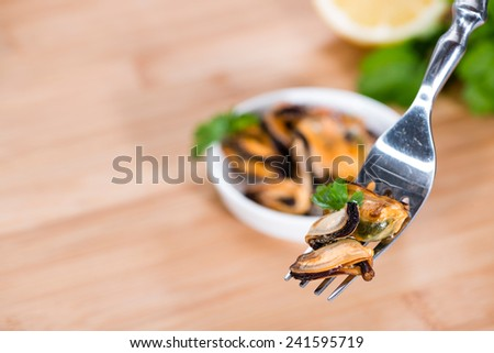 Some grilled Mussels with fresh herbs pickled on oil - stock photo