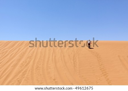 some guy is running up the dune - stock photo