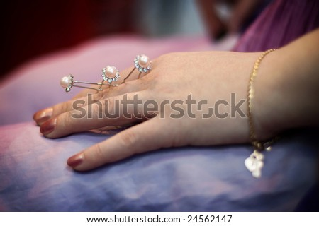 Some hairpins with pearls in a female hand