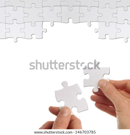 some hands hold a part of a puzzles to solve it - stock photo