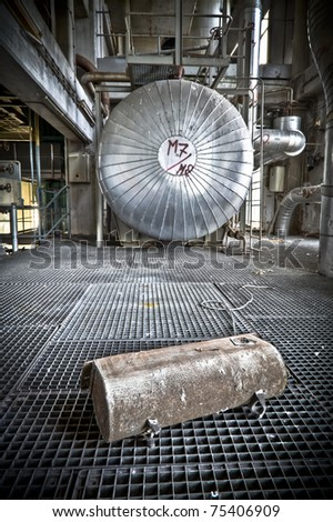 Some kind of container laying in front of this huge silo. Picture taken at an abandoned power station. A grungy industrial scene. - stock photo