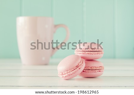 Some macarons and a pink mug on a white wooden table with a robin egg blue background. Vintage Style. - stock photo