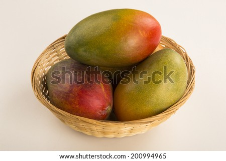 Some mangoes in a basket on a white background - stock photo