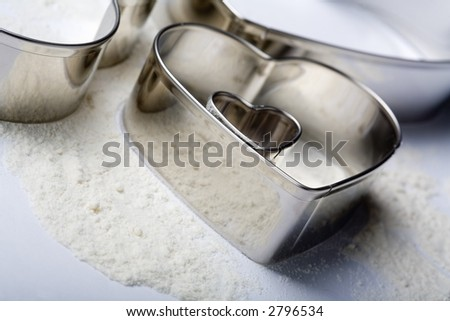 Some metal heart-cookie-cutters with some flour on white background. Tilt view. - stock photo