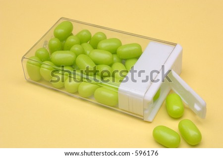 Some mints spilling from an open container - stock photo