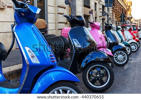 Some multi-colored scooter parked in a row at the edge of the road. - stock photo