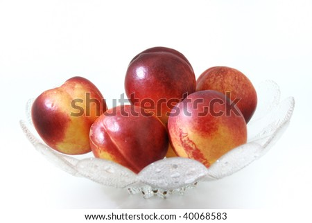 Some nectarine in a glass dish. Over white. - stock photo