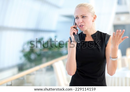 Some not good news on the mobile phone. Young and motivated businesswoman is standing and talking on the mobile phone and discussing the project issues - stock photo