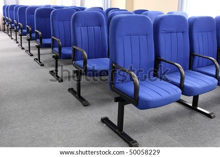 Some numbers of dark blue armchairs in the big hall