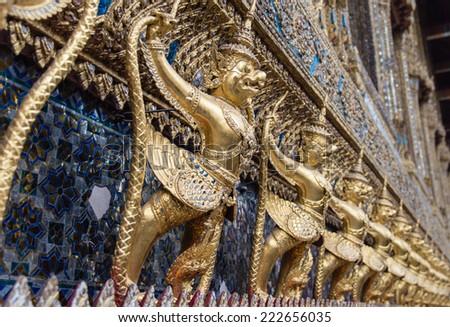Some of the golden 'garudas' (mythical beast) lining the wall  Temple of Emerald Buddha & Royal Grand Palace, Bangkok, Thailand. - stock photo