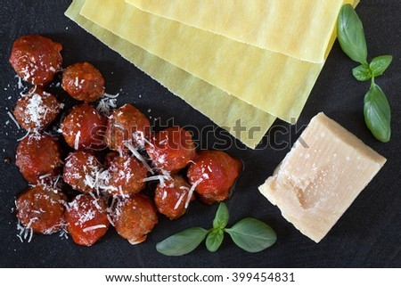 Some of the ingredients necessary to prepare lasagna following an old neapolitan recipe: raw pasta sheets, small meatballs in tomato sauce, parmesan cheese and basil. - stock photo