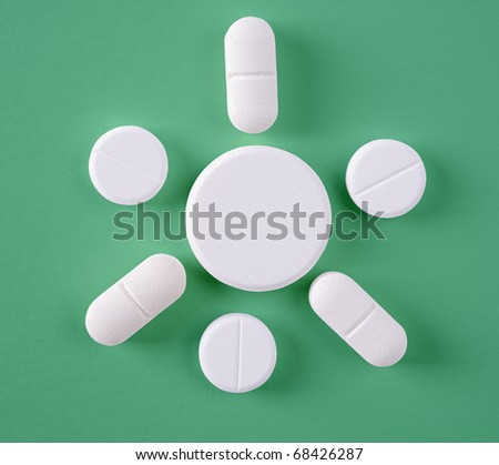 Some of White pills on a green background - stock photo