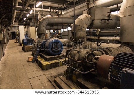 some old, dusty, pumps for hot and cold water with large electric motors