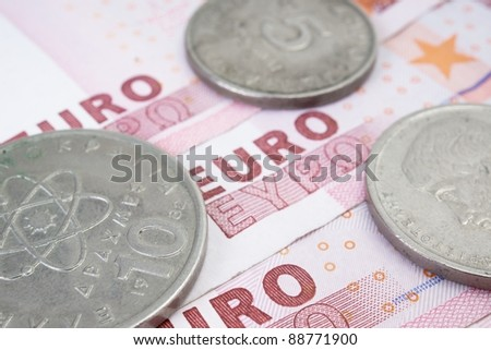 Some old greek drachma coins on euro banknotes - stock photo