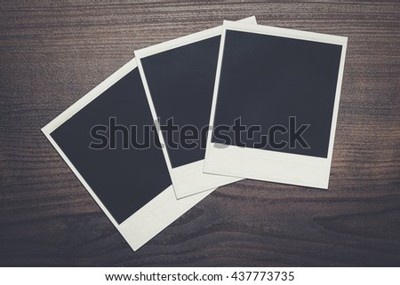 some old photos on the brown wooden table background - stock photo