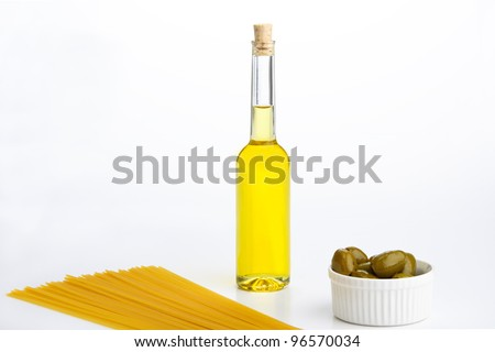 Some olives in a white dish with a bottle of olive oil in the background and some spaghetti in the foreground.shot in the studio over a white background.