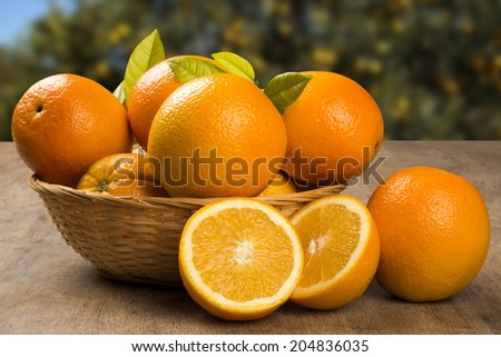 Some oranges in a basket over a wooden surface on a orange field background - stock photo