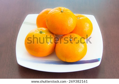 Some oranges on the white dish which is on wooden table - stock photo