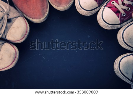 Some pairs of vintage canvas shoes in circular composition. Conceptual overhead shot with copy space - stock photo