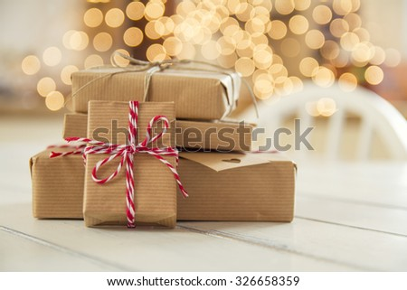 Some paper parcels (christmas gift boxes) wrapped with paper kraft and tied with red & white baker's twine in a white wooden table. Christmas lights in the background - stock photo