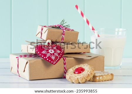 Some paper parcels wrapped (with paper kraft) tied (with red & white baker's twine) with tags, two shortbreads and a milk glass. A red heart.  A white table with a turquoise wainscot. Vintage Style. - stock photo