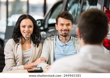 Some paperwork before buying a car. Young car salesman talking to a couple in auto salon. - stock photo