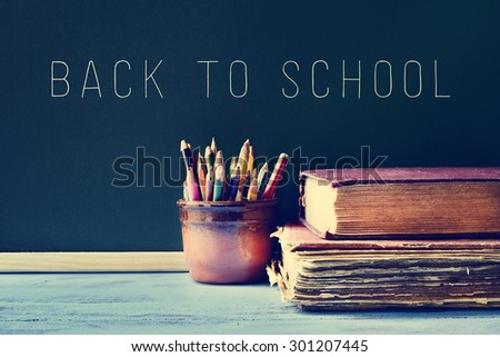 some pencils in a pot, some old books on a blue school desk, and the text back to school written on a chalkboard, with a filter effect - stock photo