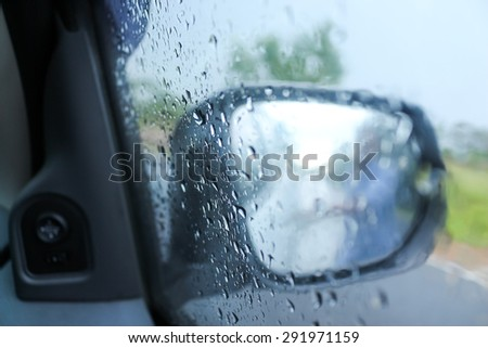 some people at  defocused rain drops on the wing mirror,The concept of safety while driving. - stock photo