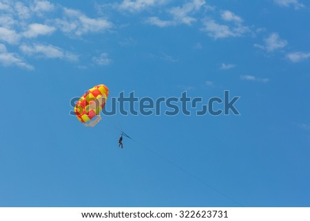 Some people parasailing over the sea - stock photo
