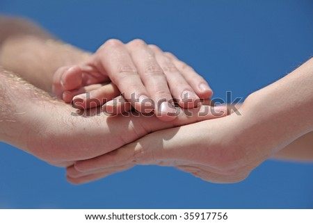 Some people putting her hands together in front of a bright blue sky. - stock photo