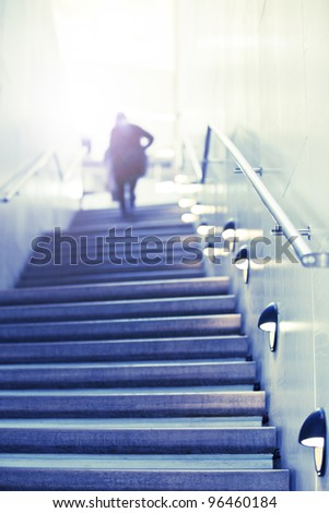 Some person walks up concrete stairs to toward the light at the top. Concept of success stairs. - stock photo