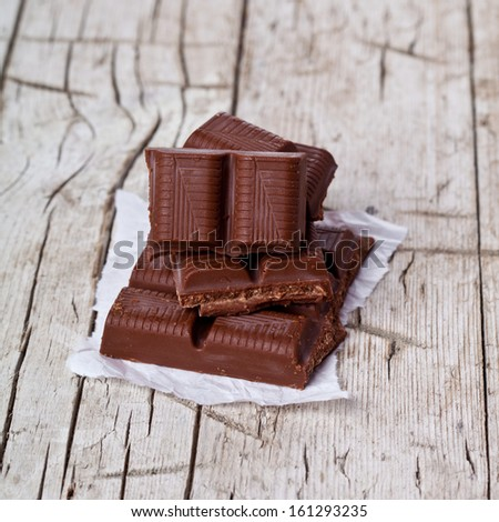 some pieces of chocolate on rustic wooden background  - stock photo