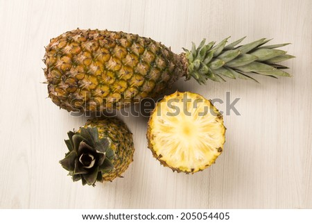 Some pineapples over a wooden table seen from above - stock photo