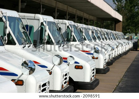 Some postal delivery trucks in line - stock photo