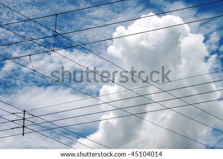 Some power lines intersecting with the blue sky and clouds in the background. - stock photo