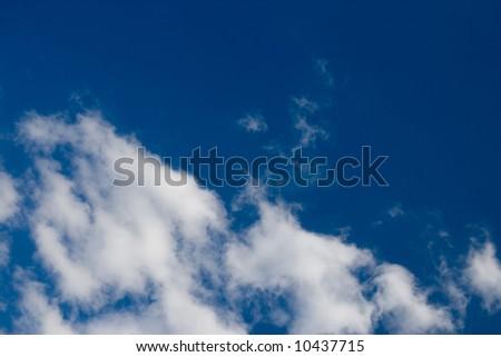 Some puffy cumulus clouds against a pretty blue sky. - stock photo